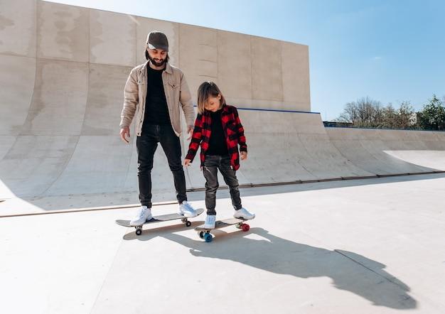 젊은 아버지와 그의 아들은 화창한 날 밖에 미끄럼틀이 있는 스케이트 공원에서 스케이트보드를 탄다.