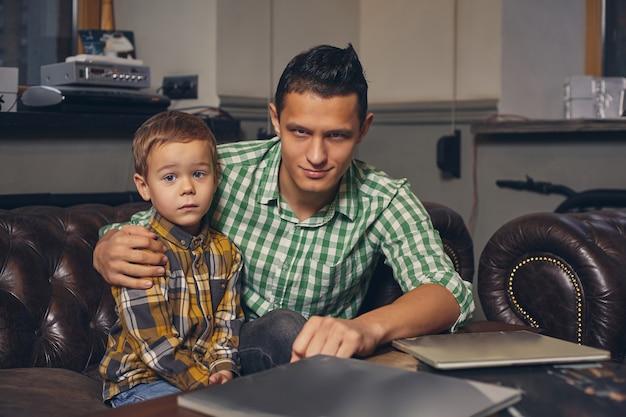 Молодой отец и его стильный маленький сын в парикмахерской в зале ожидания