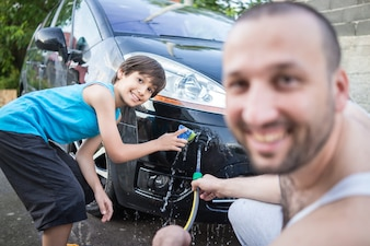 Young father and little sons washing car