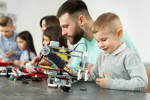 若い父と息子は、ロボット工学の学校で建設キットを組み立てます。