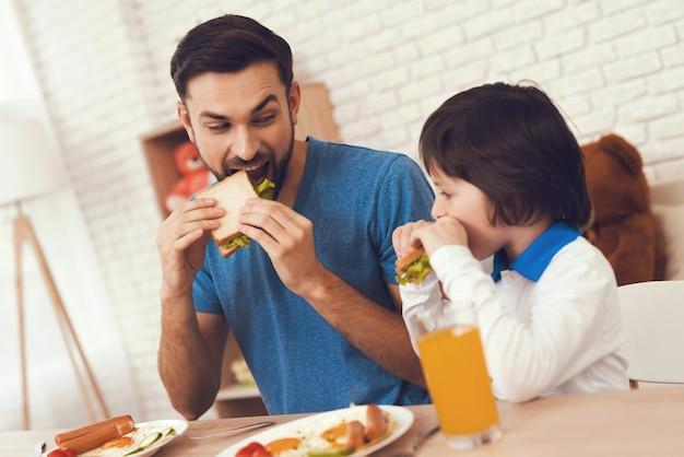 젊은 아버지와 아들은 아침을 먹습니다.
