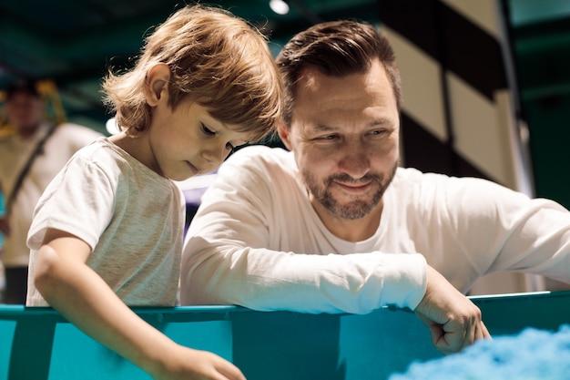 과학 및 교육 센터에 있는 젊은 아버지와 아들은 운동 모래로 작업하는 데 시간을 보냅니다. 가족 관계. 부모의 사랑과 지원. 어린이 발달 센터. 현대 레저.