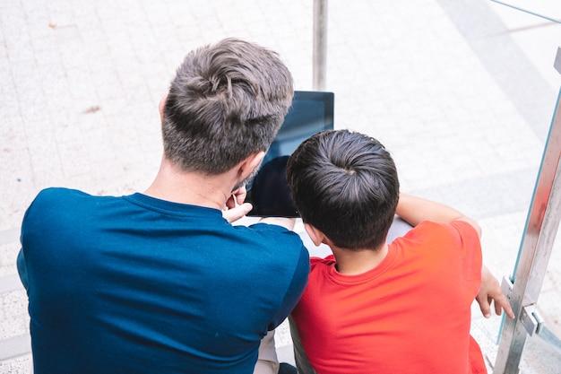 Молодые отец и сын сидят на ступеньках и играют с планшетом. концепция современных технологий. стиль жизни. фото высокого качества