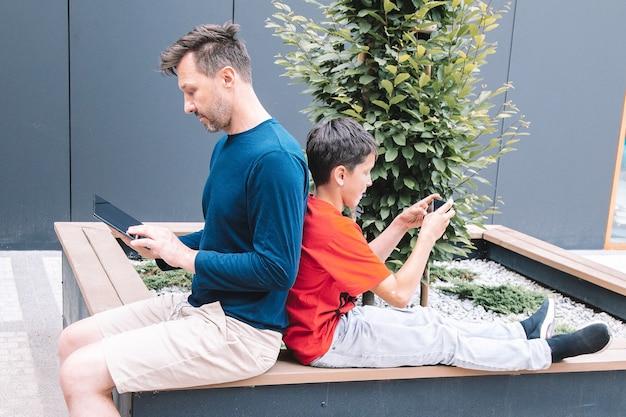 Молодой отец и сын с помощью планшета, смартфона в летний день на городской площади. концепция технологии. фото высокого качества. стиль жизни