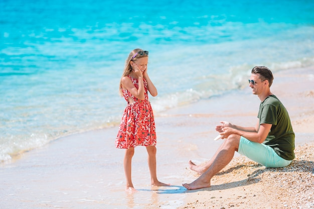 ビーチで娘の鼻に日焼け止めを適用する若い父親。日焼け止め