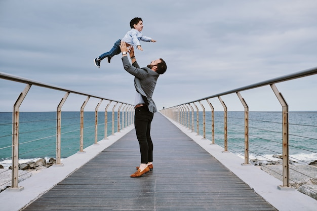 A young father on a bridge with his son flying on top of him