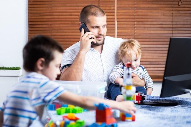 젊은 아버지 비즈니스 남자 부모는 전화로 얘기하고 집에서 일하는 동안 그녀의 아이 아들에 의해 중단됩니다.