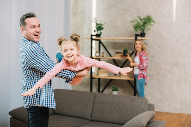 Young father carrying his daughter in living room