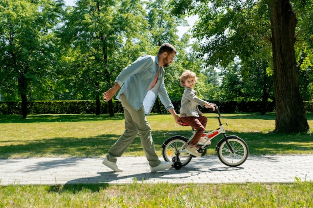 Young father in casualwear holding seat of bicycle of his adorable little son while both moving along road between green lawns on sunny day