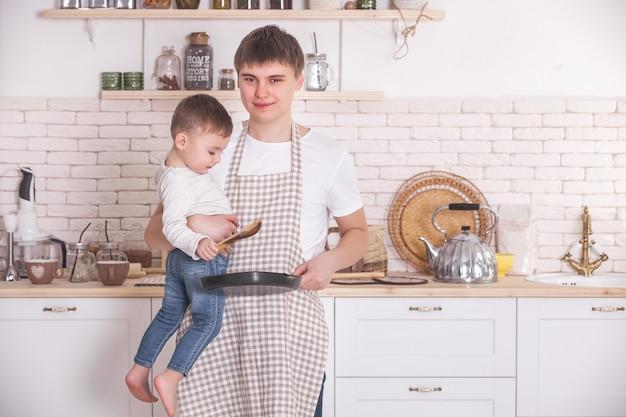 若い父親が台所で彼の小さな赤ちゃんと一緒に料理します。お父さんと息子が朝食を準備しています。小さな男の子は彼の父が料理をするのをためらいます。