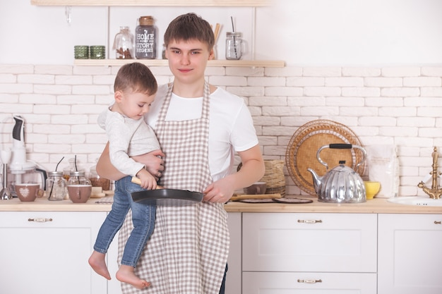 Young father cooking with his little son. dad and child on the kitchen. mothers day helpers. man with kid making a dinner or breakfast for the mother.