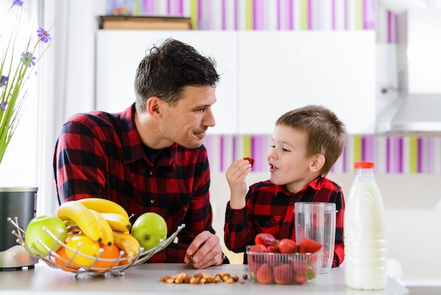 Young father and cute son sitting by the kitchen table full of fresh fruits. boy is eating strawberries.