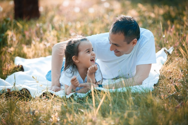 Young father and daughter lying on green grass