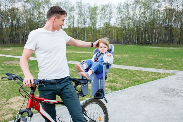 Young father and daughter riding a bicycle in the park.