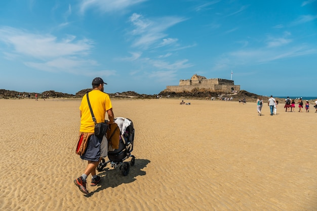 A young father enjoying the summer on the grande plage du sillon de saint-malo in french brittany, france