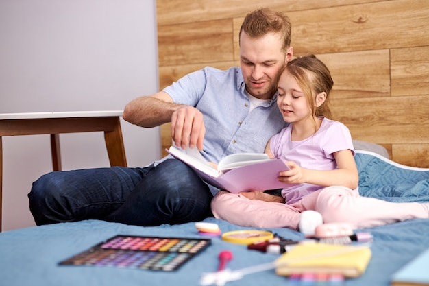 Young father explaining paragraph presented in textbook to his little daughter, she listening to him with interest