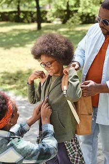 Молодой отец помогает маленькому сыну надеть рюкзак в парке во время прогулки