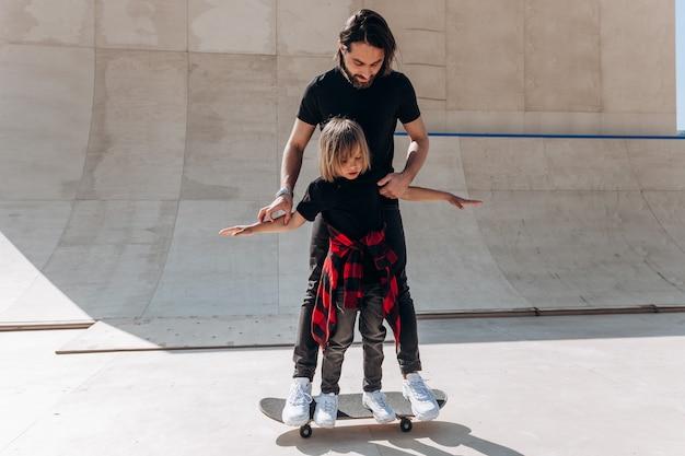 젊은 아버지는 화창한 날 스케이트 공원에서 어린 아들이 스케이트보드를 타는 것을 돕습니다.
