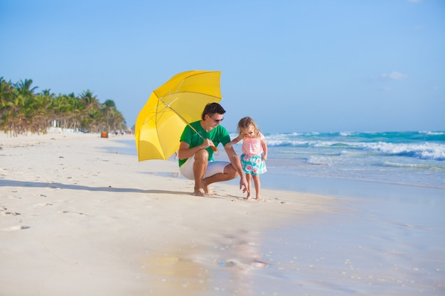 Young father and his adorable little daughter hiding from the sun under a yellow umbrella on white sunny day