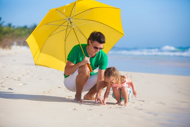 Young father and his adorable little daughter hiding from the sun under a yellow umbrella
