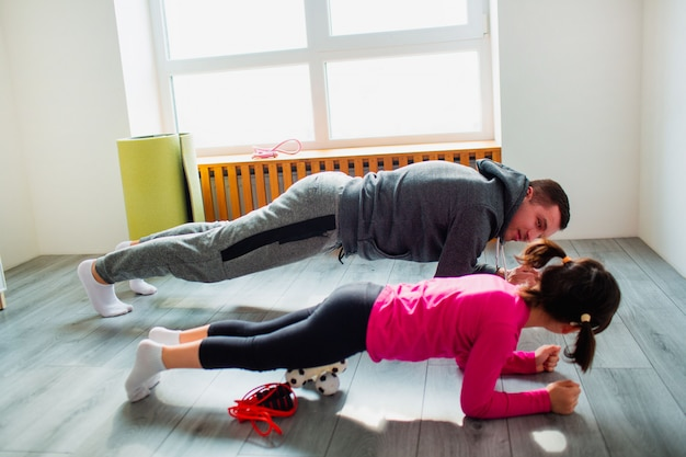 Young father and his cute little daughter are doing plank on the floor at home. family fitness workout. cute kid and daddy is training on a mat indoor and have exercises near the window in room.