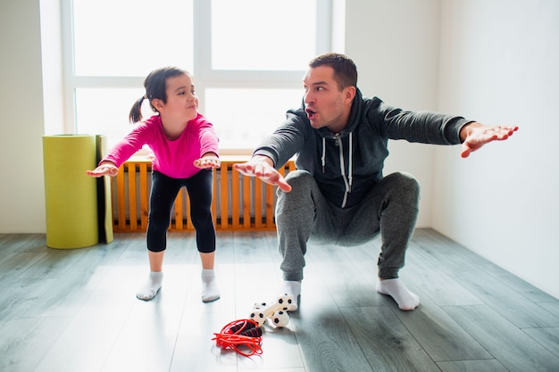 Young father and his cute little daughter are doing squat exercises workout at home. cute kid and daddy are training on a mat indoor near the window in her room