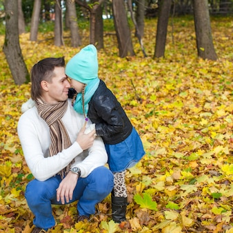 Young father and his cute little daughter whispering in autumn park