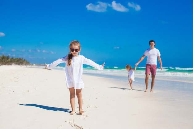 Young father and his little adorable daughters having fun on white beach