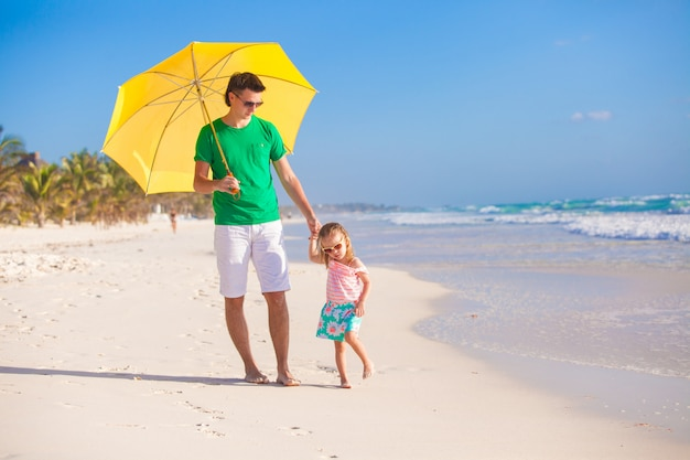 Young father and his little daughter walking under a yellow umbrella on white sand beach