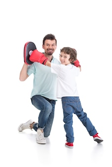 Young father and his son engaged in boxing.