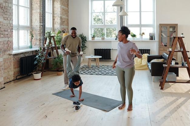 Молодой отец держится за ноги игривого маленького сына, движущегося на руках по полу, пока его активная мать в спортивной одежде тренируется рядом