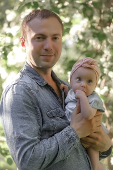 Young father holding small daughter outside in spring nature. high quality photo.