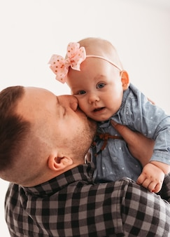 Young father holds in his arms and kisses his baby daughter on a white background