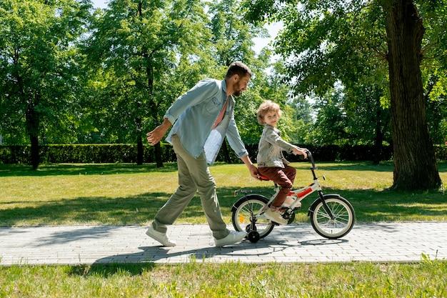 晴れた日に緑の芝生の間の道路に沿って移動しながら彼の愛らしい幼い息子の自転車の座席を保持しているカジュアルウェアの若い父親