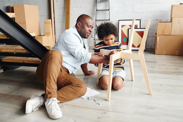 かわいい幼い息子に、床に座って部品を固定しながら木製の椅子を組み立てる方法を教えるカジュアルウェアの若い父親