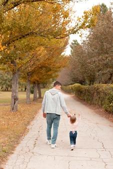 젊은 아버지는 공원에서 그의 작은 딸과 함께 걷고있다.