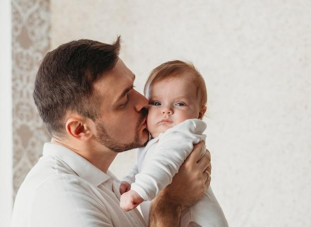 若い父は明るい部屋のクローズアップで赤ん坊の娘にキスします