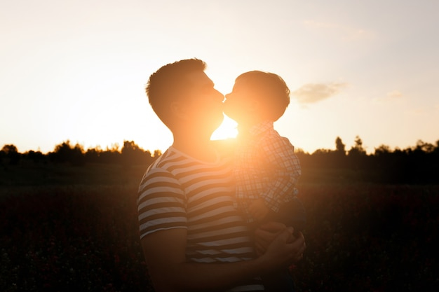 Young father kisses his toddler son on spring flower field at sunset.