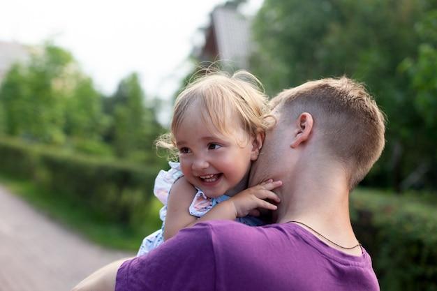 Молодой отец целует свою маленькую симпатичную дочь на открытом воздухе в летний день