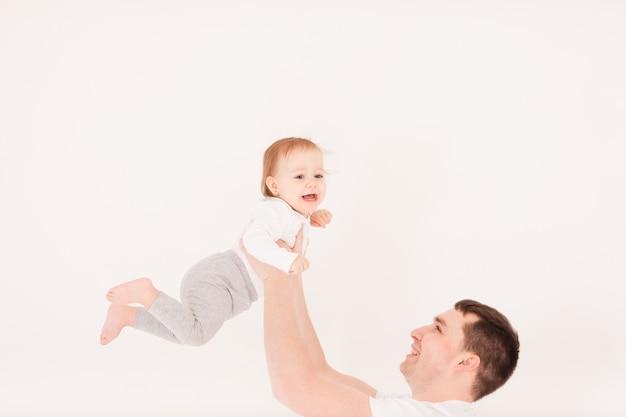 若い父親は、白で隔離された彼の小さな女の赤ちゃんを持ち上げます