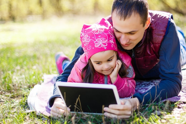 Young father and little cute daughter reading in summer park