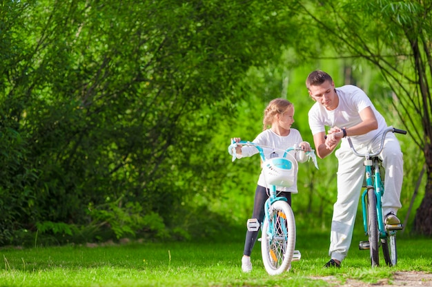 Young father and little girl biking at summer warm day. young active family ride on bicycles