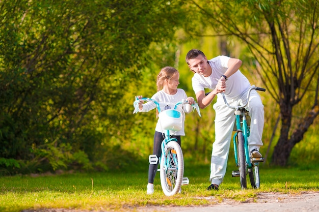Young father and little girl biking at summer warm day