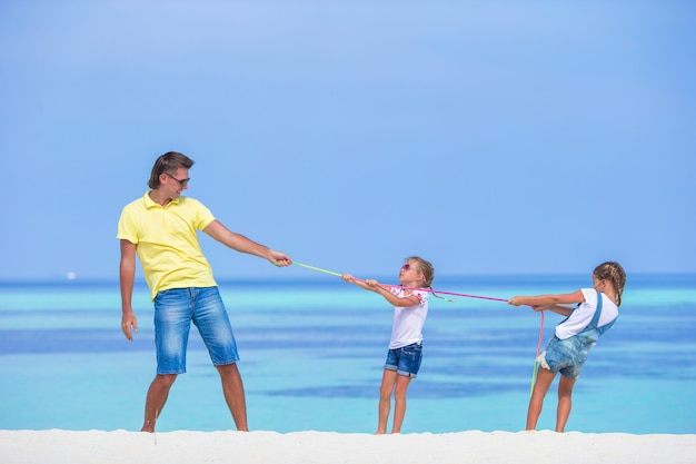 Young father and little girls have fun together during tropical vacation