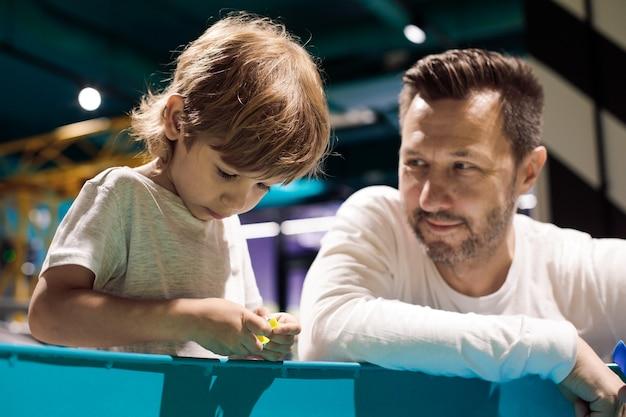 젊은 아버지는 부드러움을 가지고 노는 아들을 바라보며 발달 센터에서 함께 시간을 보냅니다. 부모의 사랑과 지원. 어린이 발달 센터.