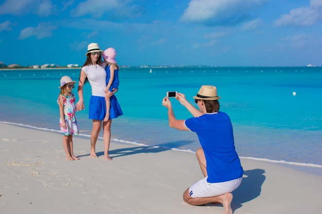Young father making photo on phone of his family at the beach