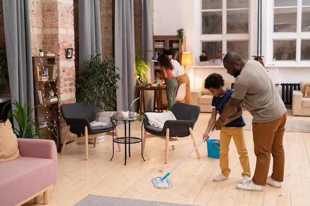 어머니와 딸이 함께 테이블을 청소하는 동안 거실에서 바닥을 씻는 방법을 어린 아들에게 보여주는 아프리카 민족의 젊은 아버지