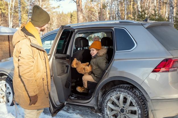 田舎への旅行中に後部座席に座っている冬服で彼の愛らしい小さな娘のために車のドアを開ける若い父親