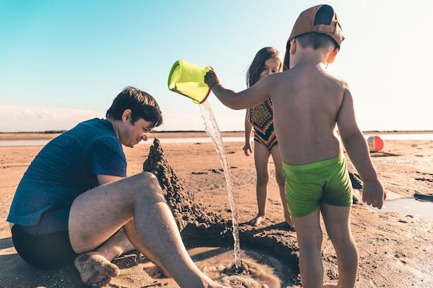 해변에서 아이들과 노는 젊은 아버지. 라이프 스타일 톤 사진