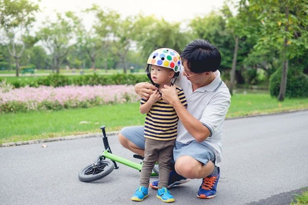 Young father put helmet on little asian 2 year old toddler boy child, dad and son having fun with balance bike (run bike) on nature at park, dad tech son to ride bike